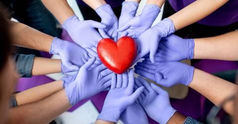 Groep handen van mensen met handschoenen aan dragen een hart